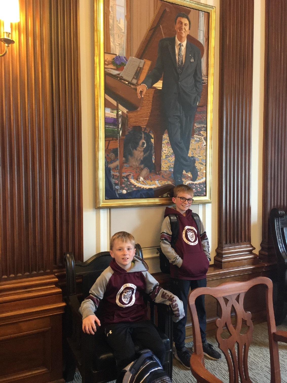 Conor and Owen pose in Governing Council Chambers in front of C. David Naylor and Oscar T. Naylor.